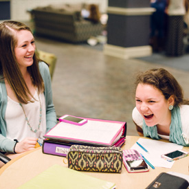 two students laughing around a table with binders and notes upon it
