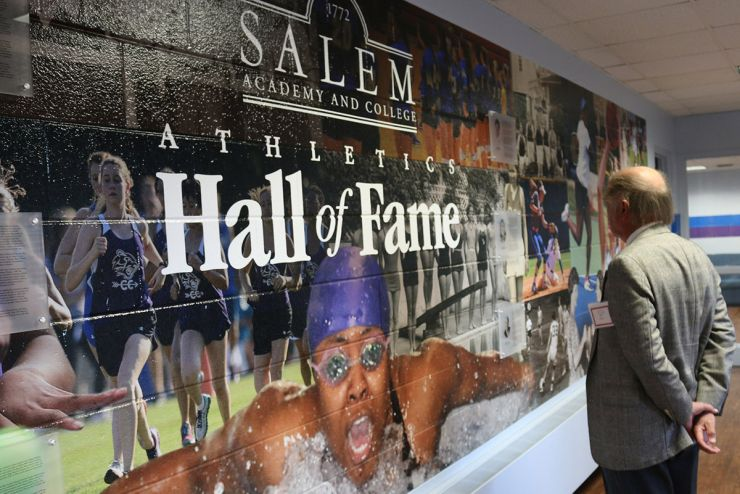 Hall of Fame - gentlemen studies the collage wall honoring Academy athletes over the years