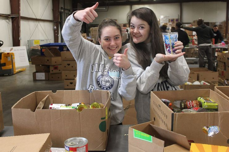 Community Service - Students packing boxes of food for the hungry